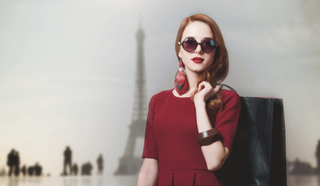 Redhead woman with shopping bags with Eiffel tower on background