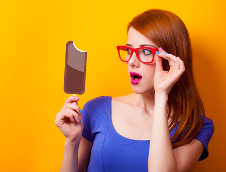 Portrait of a young redhead girl with chocolate ice-cream on yellow background Stock Photo