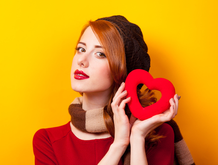Portrait of a young redhead girl with heart shape toy on yellow background