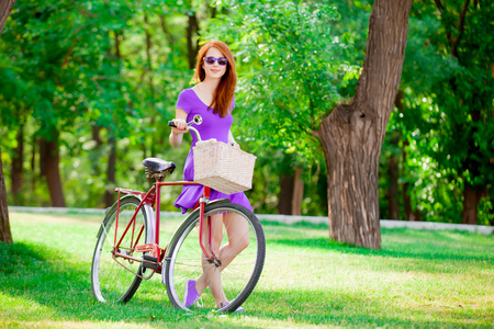 Young redhead girl with bike at summertime outdoor