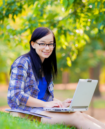 Young brunette student girl with laptop computer studying on green grass in summertime