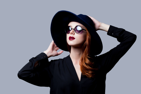 Young redhead girl in dark style in sunglasses and hat on grey background