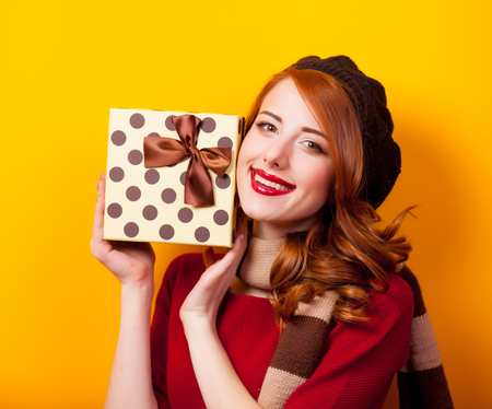 Portrait of a young redhead girl with present box on yellow background