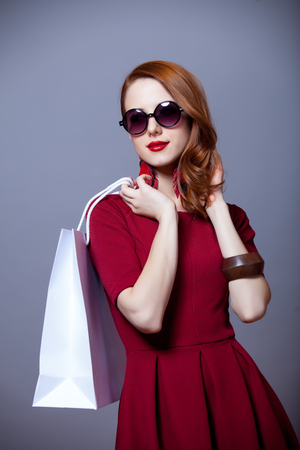 Redhead woman in red dress with shopping bags on grey background Stock Photo