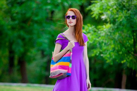 Young redhead girl in purple clothes and sunglasses in the summertime park