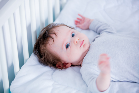 Little boy lying down in white bed 스톡 콘텐츠