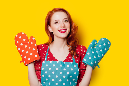 Redhead housewife with gloves and apron on yellow background Standard-Bild - 97441363