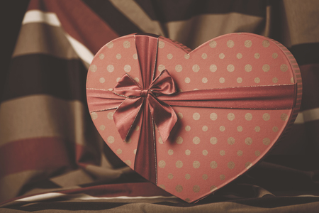 Vintage striped heart shape box. Image in old color style Imagens