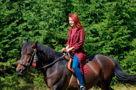 Redehad girl with horse in the forest at summertime