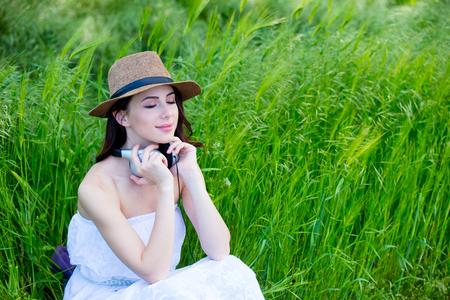 Beautfiul girl with headphones at wheat field in summertime season Stock Photo