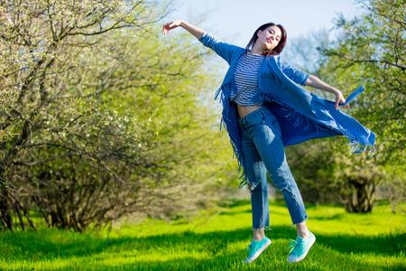 Young girl in blue clothes at springtime garden. Sunny day