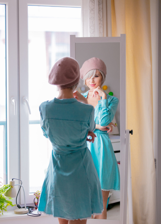 Young girl in beret with short hairs dressing up near mirror at home. Stock Photo