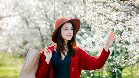 Young girl with hat and shopping bag at blossom green garden in springtime