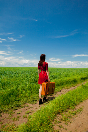 Beautfiul redhead girl with suitcase at wheat field in summertime season. Backside view