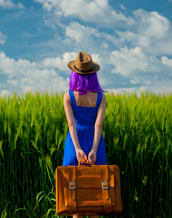 Beautfiul purple hair girl with suitcase standing at wheat field in summertime season. Backside view