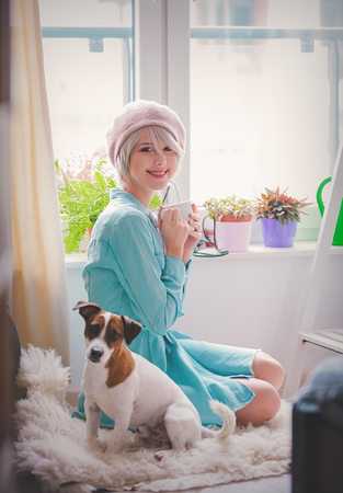 Young girl with cup and dog at home in sunny day.