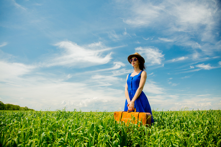 Beautfiul redhead girl with suitcase standing at wheat field in summertime season
