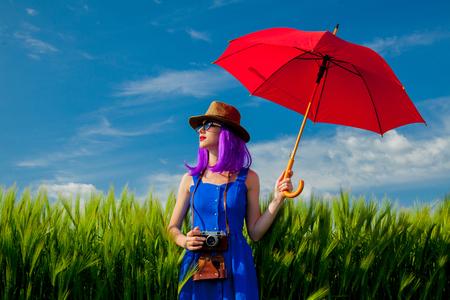 Beautfiul purple hair girl with umbrella at wheat field in summertime season