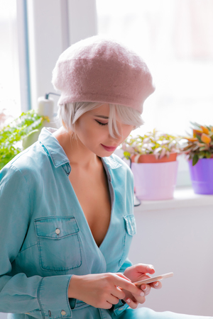 Young girl in beret with short hairs using a mobile phone at home Stock Photo