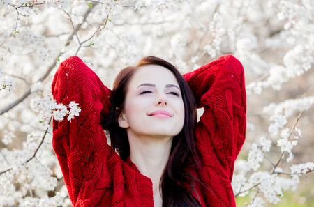 Young girl in red cardigan in blossom trees garden in springtime