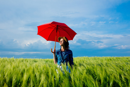 Beautfiul redhaired girl with umbrella at wheat field in summertime season
