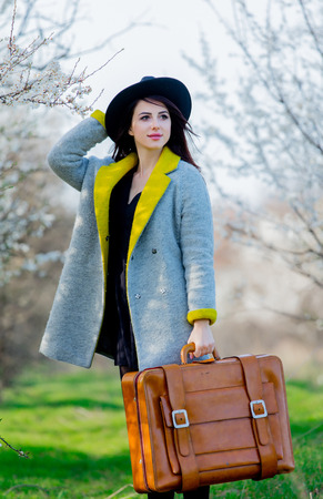 Young redehad girl in coat and hat with suitcase on springtime outdoor