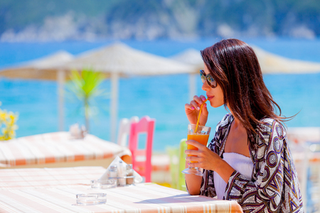 Beautiful tourist woman drinking a juse in a restaurant on sea beach in Greece.
