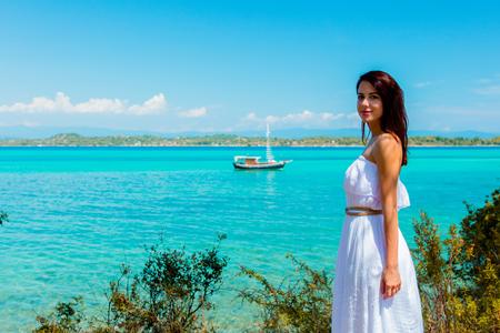 Young beautiful girl posing in a hat near a boat in sea in Greece