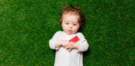Small boy laying on fresh green grass with flag of Poland