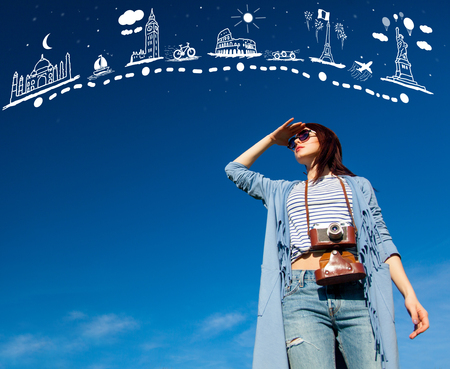 portrait of the beautiful young woman with camera on the sky background and abstract travel map in air