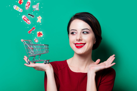 Portrait of young happy woman with shopping basket on green background