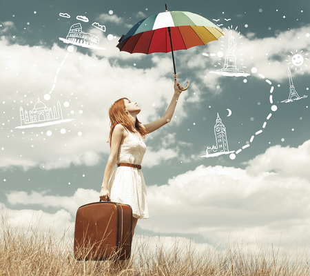 Beautiful redhead girl with umbrella and suitcase at outdoor with astravet travel map.