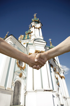 handshake of two conflict people with Church on background Stock Photo