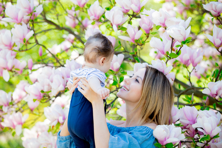 Young redhead mother and child have a leisure in springtime flowering Magnolia garden in sunny day.
