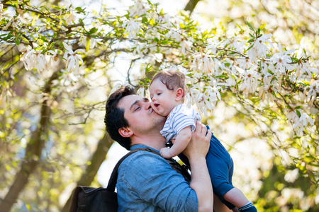 Young father with child have a leisure in springtime flowering garden in sunny day.