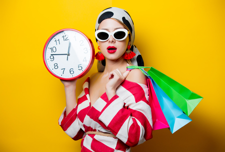 Portrait of beautiful style woman in sunglasses and striped clothes with alarm clock and shopping bags on yellow background