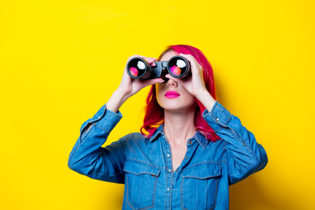Young pink hair girl in blue shirt holding a binoculars. Portrait on isolated yellow background Фото со стока - 101056546