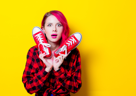 Young pink hair girl in red tartan shirt and gumshoes. Portrait isolated on yellow background