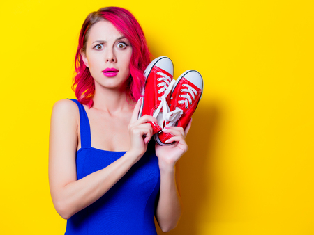 Young pink hair girl in blue dress with gumshoes. Portrait isolated on yellow background Фото со стока