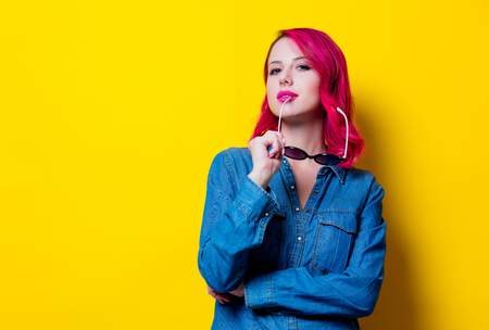 Young pink hair girl in sunglasses and blue shirt. Portrait on yellow background Фото со стока