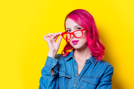 Young pink hair girl in blue shirt and red glasses. Portrait isolated on yellow background
