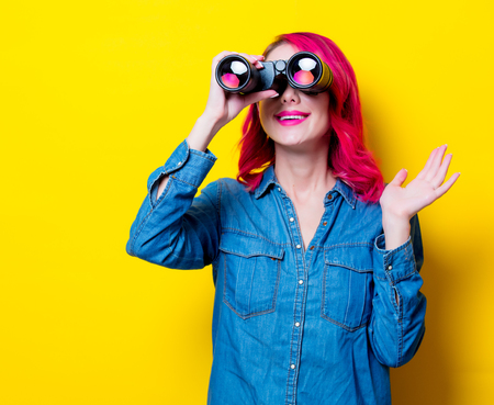 Young pink hair girl in blue shirt holding a binoculars. Portrait on isolated yellow background
