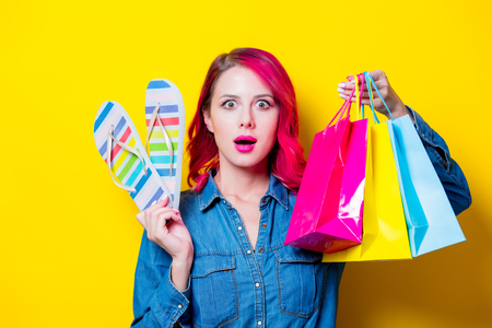 Young pink hair girl in blue shirt holding a colored shopping bags and flip flops. Portrait on isolated yellow background Foto de archivo
