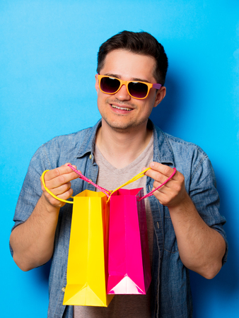 Young man in sunglasses holding a shopping bags on blue background