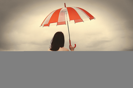 Girl with umbrella at field in rainy day. Image made in vintage style