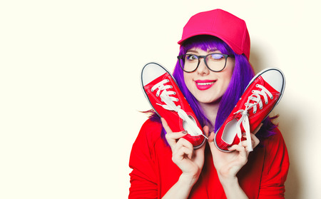 portrait of beautiful smiling young woman with red gumshoes Stock Photo