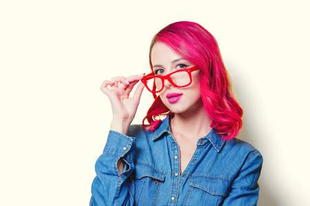 Young pink hair girl in blue shirt and red glasses. Фото со стока