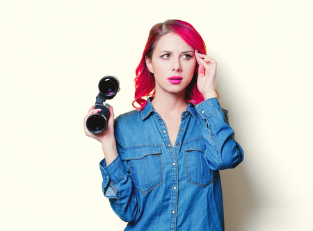 Young pink hair girl in blue shirt holding a binoculars.