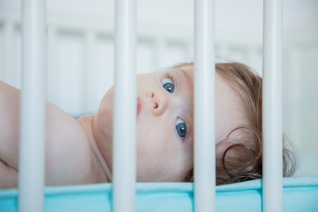 Little baby lying down in a bed at home. Image made with natural lite. Stock Photo