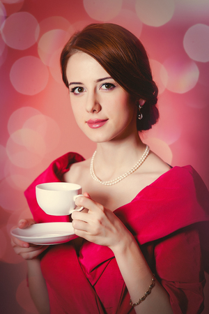 Young redhead woman in red Victorian epoch clothes with cup of tea on pink background with bokeh